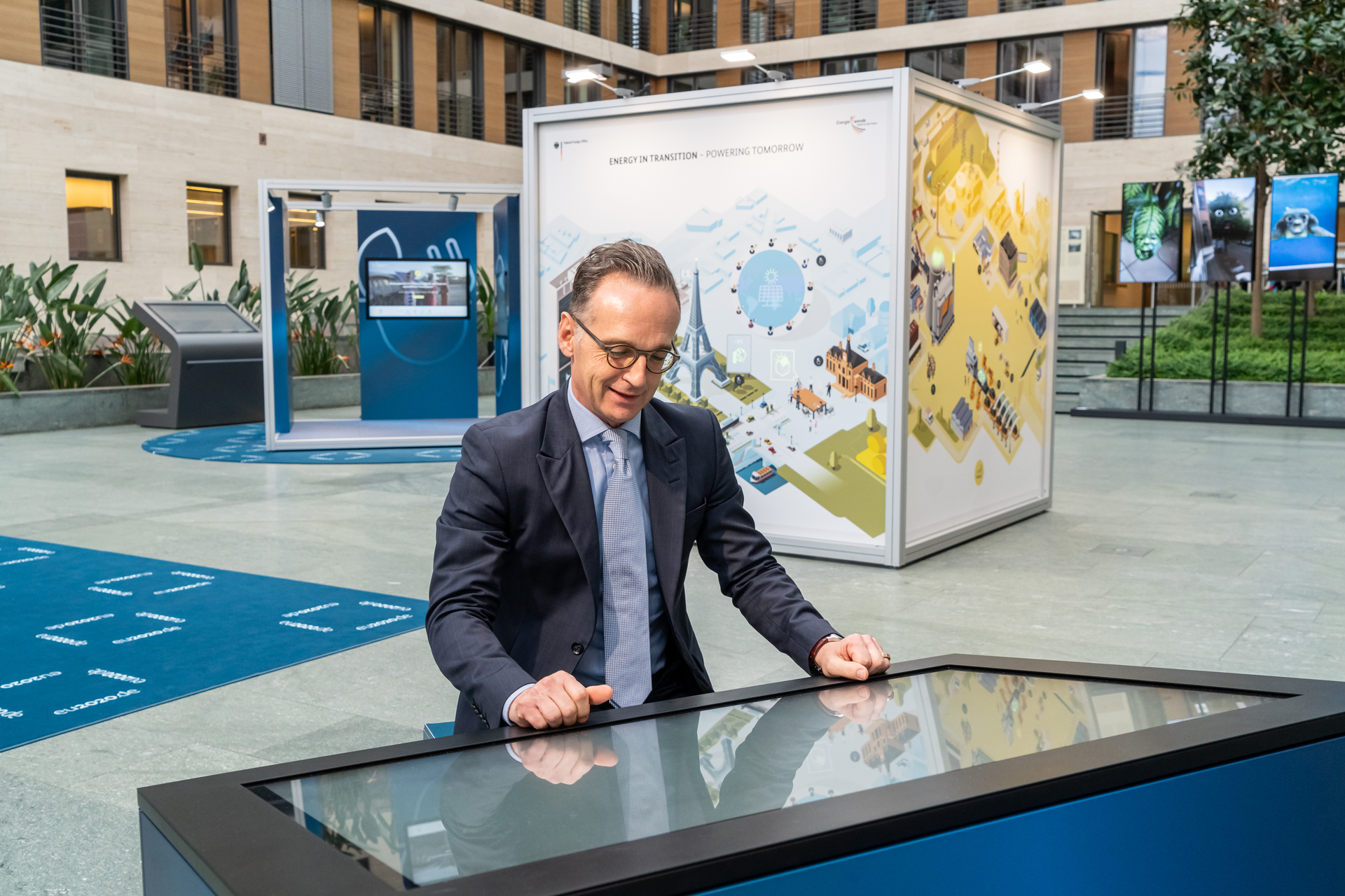 German Foreign Minister Heiko Maas is sitting at a monitor at the Mobility station and is viewing the content of this part of the exhibition on the global transformation of transport.