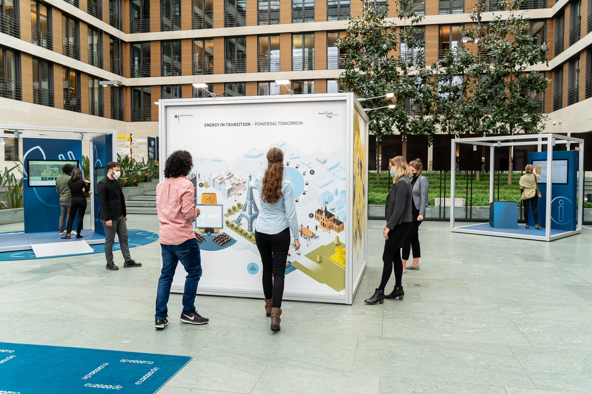 A snapshot of visitors at the travelling exhibition. The cube-shaped Energy in Transition station is in the foreground. Visitors are standing at the different sides of the cube and are pointing at and viewing the cube's animations that are lighting up. In the background you can see visitors standing at the other stations.