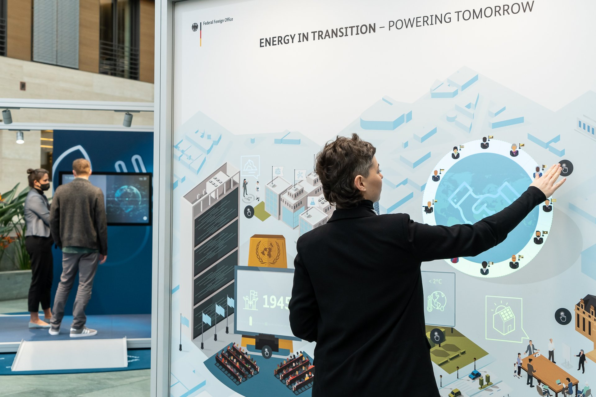 A woman stands at the Energy in Transition station of the exhibition and starts up the animation. In the background a woman and a man are standing in front of a monitor at the Renewable Energy station.