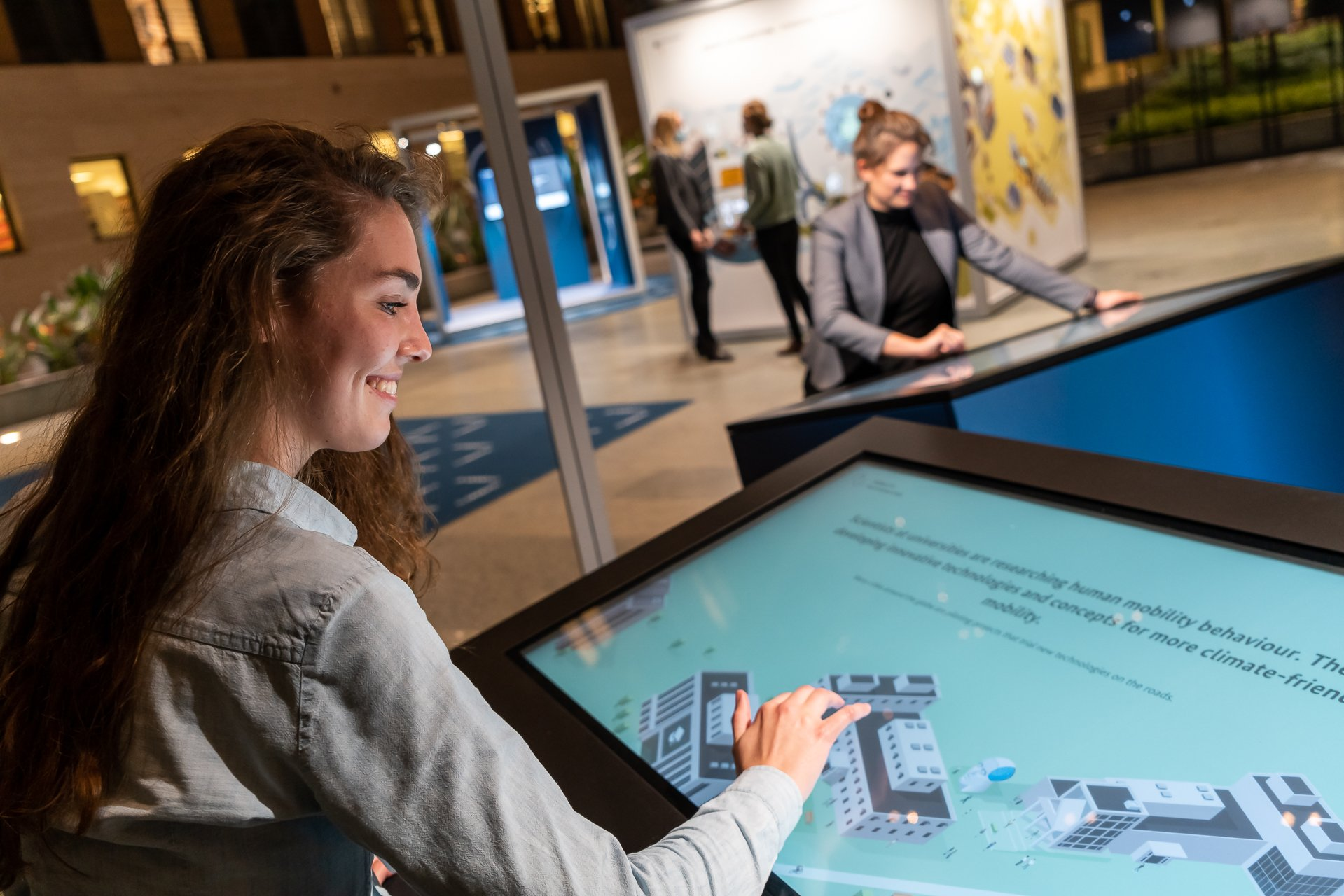 A woman visiting the travelling exhibition is sitting at a monitor at the Mobility station and is viewing the content of the science perspective.
