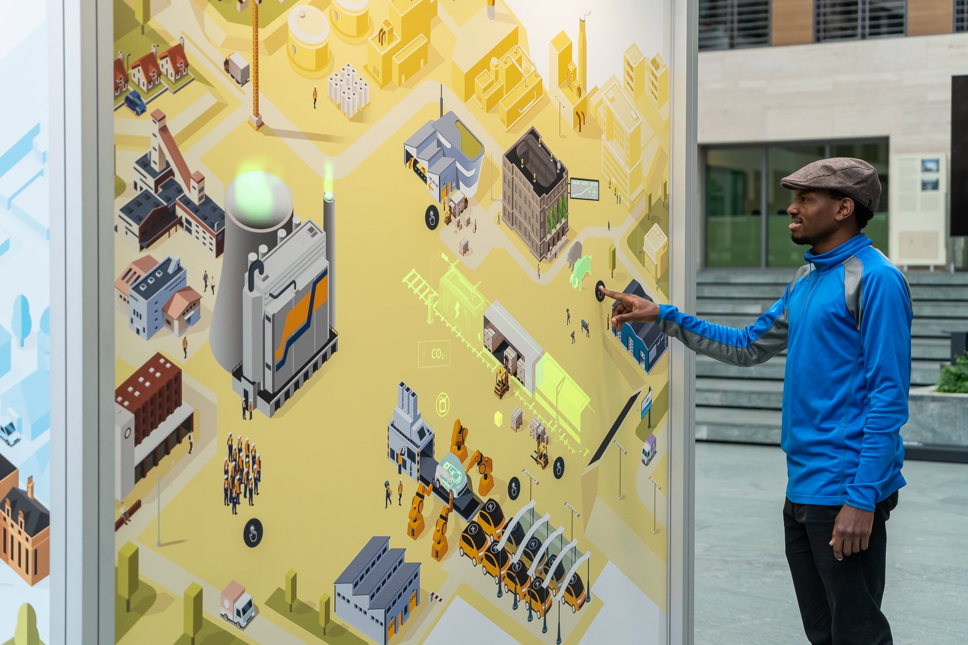 A visitor starts up the animation at the Energy in Transition station and is fascinated by the light-up display of a freight train powered by electricity and an electric car on a production line.